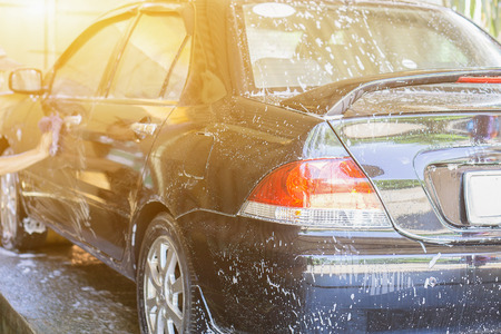 car washing by hand using a foam preparation for polishing,cars in a carwash,selective focus,vintage color Stock Photo
