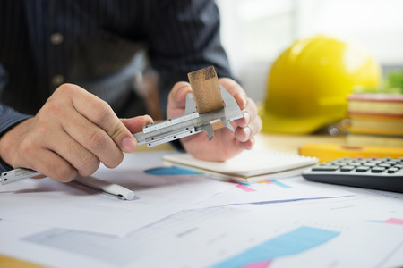 architect work concept.man working with new startup project in modern loft. Drawning pen,inspection engineer report with product and vernier calipers,engineer architectural project,Notebook on table