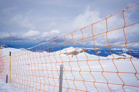 chainlink fence: protection net,Ski slope run safety net mesh mountain protection wall fence,wire fence and snow. chain-link fence. wire mesh fence in the snow. texture, background,selective focus,vintage color