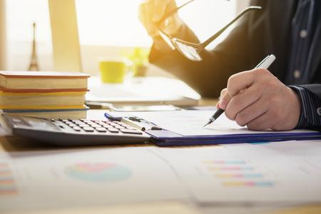 左手、デスクでペンとのテーブルで本を読むと書いているその男は、論文を書く人の実業家署名契約の署名、契約フォームを男します。オフィスで 写真素材