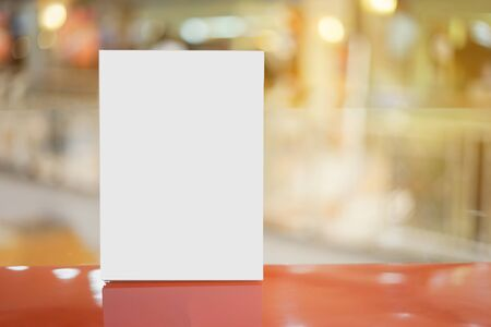 sign holder: Mock up Menu frame on Table in Bar restaurant cafe,Stand for booklets with white sheets of paper acrylic table tent card mockup on wooden table on cafe teria ,can be used for montage or display