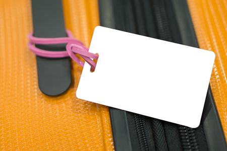 Close up of blank luggage tag label on suitcase or bag with TRAVEL INSURANCE ,Can be used for montage or display your products,selective focus,vintage color Stock Photo
