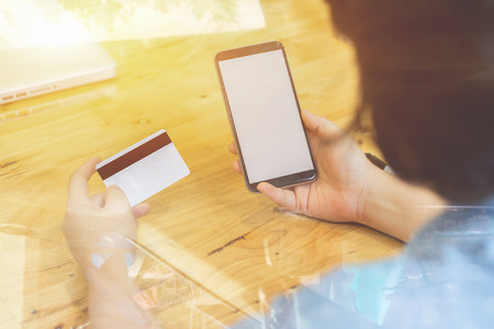 Woman verifies account balance on smartphone with mobile banking application.Online payment,Womens hands holding a credit card and using smart phone for online shopping,selective focus,vintage color