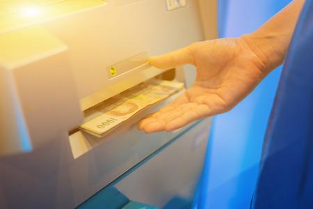 automatic transaction machine: Mano de la mujer que retira el dinero de cajero automático del banco de interior, mano que consigue baht tailandés billetes en cajero automático en el foco de bank.selective, color de la vendimia Foto de archivo