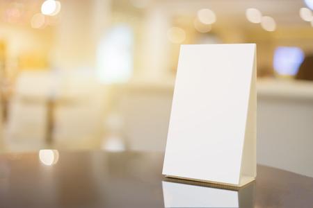 紙アクリル テーブル テント カード モックアップ カフェぼやけた映像の背景に木製のテーブルの上の白いシーツで小冊子のスタンド レストラン カ 写真素材