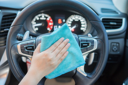 valeting: Hand with microfiber cloth cleaning car.woman cleaning car interior - car detailing and valeting concept in car wash car care station ,selective focus,vintage color Stock Photo