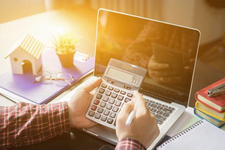 De negocios que analiza listas de inversión con el ordenador portátil calculadora. Estadísticas y tecnología en las personas office.Business usando la computadora portátil en la oficina, Analizar enfoque plans.selective, el color de la vendimia