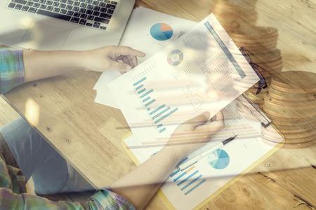 Geschäftsmann, der Finanzdaten mit Grafiken und Diagrammen während der Arbeit an einer Laptop-Computer, junger Unternehmer analysiert sein Notizbuch, Münzen, männliche Freiberuflerarbeit im Café, selektiver Fokus