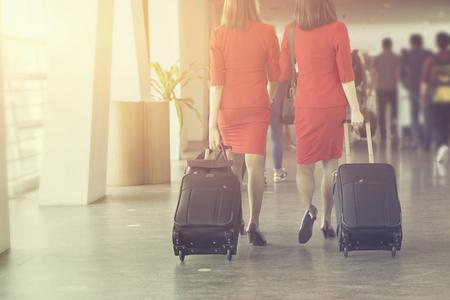 I padroni di casa, le donne che tirano la valigia nel moderno terminal dell'aeroporto. Viaggiare indossando abiti di stile rosso camminando via con il suo bagaglio mentre aspettano il trasporto. Messa a fuoco selettiva, colore dell'annata