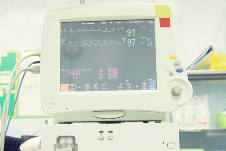 convalescing: EKG monitor in intra aortic balloon pump machine,Heart blood pressure monitor used in a hospital room for Patient monitoring machine beside bed in hospital ward,selective focus,blue tone color.