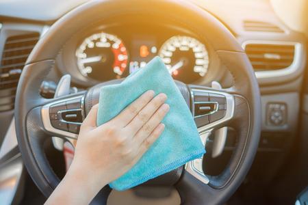 Hand mit Mikrofasertuch Reinigung car.woman Auto-Innenreinigung - Auto Detaillierung und valeting Konzept in Autowaschanlage Autopflege, selektiver Fokus, Jahrgang Farbe Standard-Bild