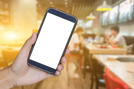 Man hand holding mobile smart phone , tablet,cellphone over Blur or Defocus image of Coffee Shop or Cafeteria,Customer at restaurant blur background with bokeh ,vintage color,food online call shopping Imagens