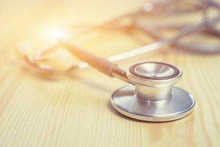 Estetoscopio sobre la mesa de madera, dispositivo médico acústico para la auscultación, o escuchar los sonidos internos de un cuerpo humano o animal, que se utiliza para escuchar a los intestinos y el flujo sanguíneo en las arterias y las venas.