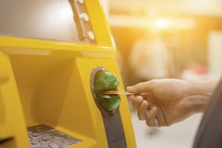 automatic transaction machine: Dé la inserción de tarjeta de cajero automático en la máquina de banco para retirar dinero, la gente de pie en una cola para usar los cajeros automáticos de un banco. Persona que recibe dinero del color de ATM.vintage