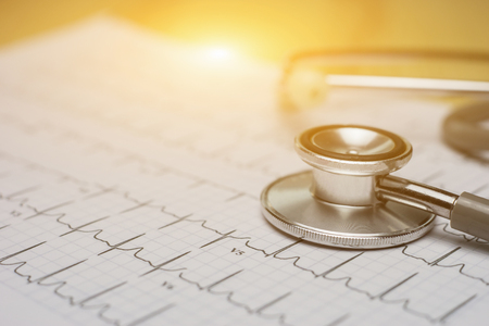 doctor workplace with a stethoscope at wooden table,Cardiogram chart with medical stethoscope and on table closeup,for Surgeon doctor Medical heart,selective focus,vintage color.morning light Stock Photo