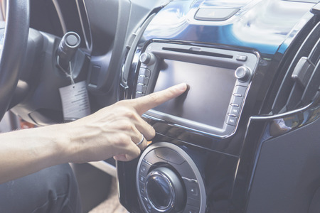 gprs: Transportation,technology and vehicle concept - man using car system control pushing panel button screen interface modern design Stock Photo