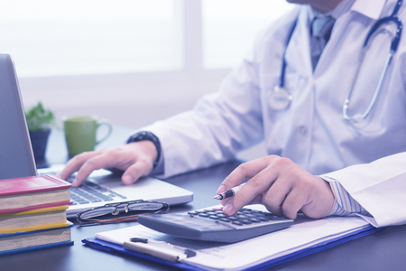 young medical doctor caucasian healthcare professional wearing a white coat with stethoscope in hospital ,doctors office calculates on an electronic calculator,selective focus,blue color