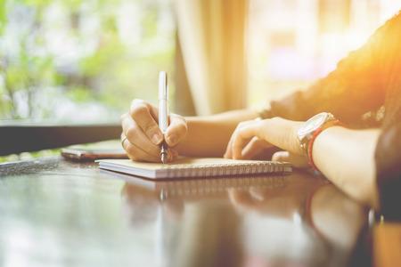 weibliche Hände mit Stift schriftlich auf Notebook auf Holztisch, junge Mädchen schriftlich in ihr Tagebuch, in den Park, Frau schreiben Empfänger Adresse auf Mailing Umschlag, weibliche Hände Senden Brief, Vintage Farbe Standard-Bild