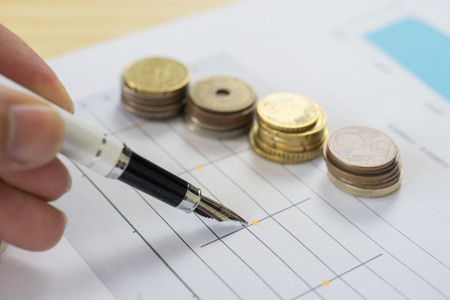 Finances statement with Pen,hand pointing pen on financial charts, paper work in the office,Finance Business,discussing on stock market charts pens pointing at business document during discussion Stock Photo