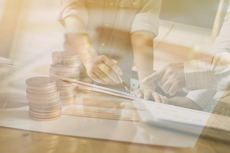 person writing: Double exposure of person pointing writing goals on a paper,writing business plan at workplace,man holding pens ,papers,notes in documents,Saving money concept,graph, stacks of coins ,chart and pen Stock Photo