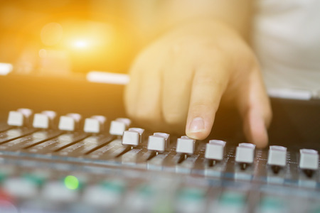 studio working with sound and light mixer console,hands of sound engineer working on recording studio mixer,Expert adjusting the volume of a sound mixer audio mixing console with mixer board,vintage