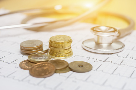 Coins money with medical expenses label, financial concept. Vintage color wooden background with dramatic light.Cost of health care concept, stethoscope and calculator on document, in the savings,