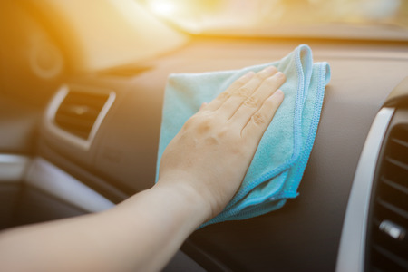 valeting: Hand with microfiber cloth cleaning car.woman cleaning car interior - car detailing and valeting concept in car wash car care station ,selective focus
