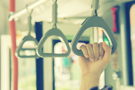 transportaion: Handle on ceiling of bus,handle on a train,The handle on the MRT, prevent toppling.underground railway system or metro,people holding onto a handle on a train and the bus,selective focus,vintage color