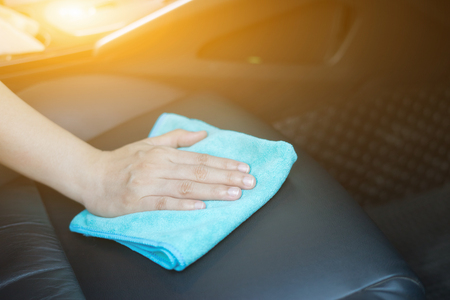 Hand with microfiber cloth cleaning car.cleaning leather car seat with microfiber cloth,auto detailing and valeting concept,cleaning car interior,car wash carcare station,selective focus,vintage color Фото со стока