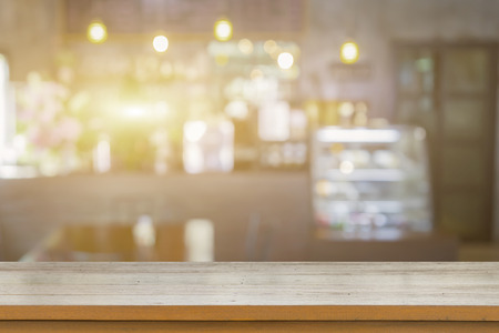 Empty brown wooden table and Coffee shop interior with some people meeting and blur background with bokeh light image,can be used for montage or display your products