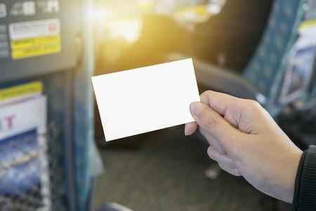 両手白ビジネス訪問カード、ギフト、チケット、パス、現在クローズ アップの駅、地下鉄、プラットフォームの背景に電車を待つ人のぼやけていま 写真素材