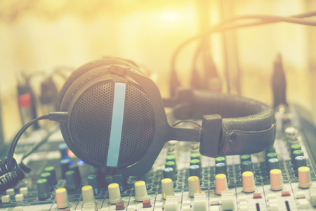 Dj equipment in a studio working with sound and light mixer console ,headphones resting on the top,boutique recording tools  desk,selective focus,vintage color Stock Photo