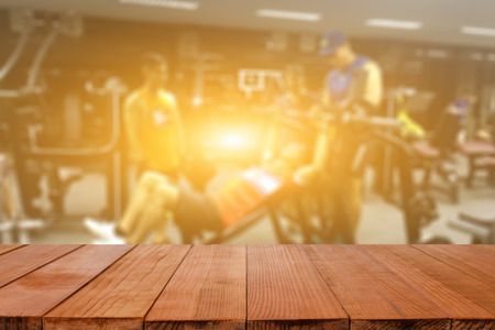 Empty brown wooden table top on blurred background of fitness gym,Young People group of women and men doing sport in the gym for fitness,interior of new modern gym with equipment