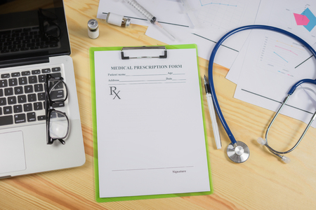 syring: Top view of modern, sterile doctors office desk. Medical accessories,stethoscope laptop pen syring and vaccineprescription with copy space around products.clip board, glasses and other things