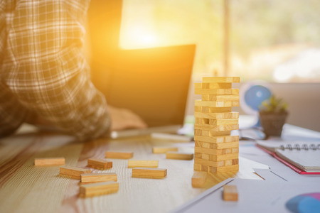 Planning, risk and strategy in business, businessman gambling placing wooden block on a tower,construction with copy space. man plan a project using laptop in background,selective focus,vintage color