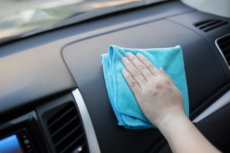 Hand with microfiber cloth cleaning leather seat,auto detailing and valeting concept,washing car care interior,selective focus,vintage color 版權商用圖片