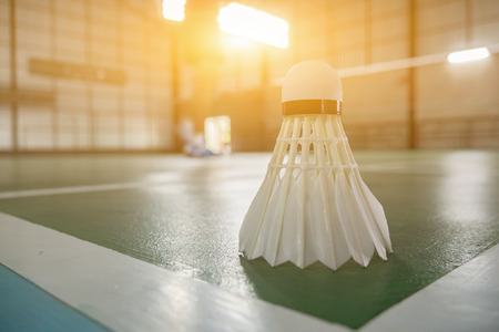 shuttlecock: A set of badminton concept.Badminton ball (shuttlecock) and racket on court floor,Paddle and the shuttlecock and badminton courts with players competing in modern gym,selective focus,vintage color