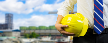 engineering management construction concept,engineer holding  hand a  yellow helmet and measure equipment security,Architects overseers on working site background ,for banner in website