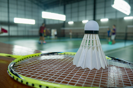 A set of badminton concept.Badminton ball (shuttlecock) and racket on court floor,Paddle and the shuttlecock and badminton courts with players competing in modern gym,selective focus,vintage color