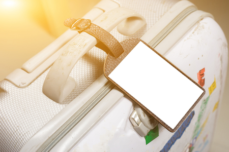 insurer: Close up of blank Leather luggage tag label on oid suitcase or bag with TRAVEL INSURANCE ,Can be used for montage or display your products,selective focus,vintage color Stock Photo