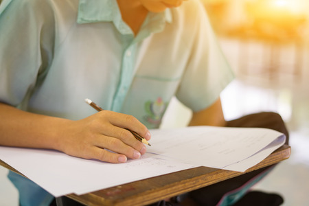 Student hand holding pen writing doing examination with blurred abstract background university  boy  in uniform attending exam classroom educational school:  college people in room vintage color
