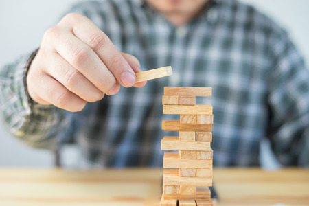 Planning, risk and strategy of project management in business, businessman and engineer gambling placing wooden block on a tower,construction with copy space,selective focus,vintage color Stock Photo
