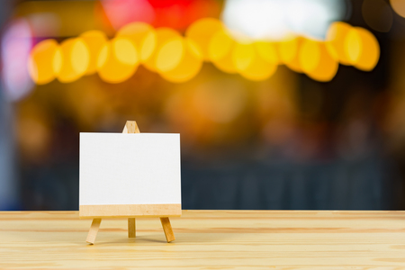 Easel with blank canvas on wooden table,billboard on wood desk top with supplied bokeh background,Template mock up for montage of display your product.vintage color Stock Photo - 72636121