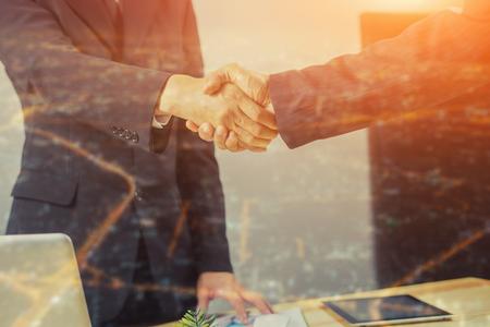 Doppelbelichtung von Great Job, Ein Deal versiegeln, Erfolgreiches Geschäft, Händedruck, Geschäftsmann zusammen, Gute agreement.two Menschen schütteln die Hände stehen am Arbeitsplatz in der Stadt scape