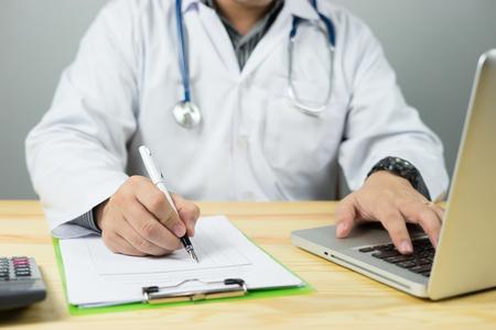 profesional de la atención sanitaria caucásica joven estudiante médico vistiendo una bata blanca con estetoscopio en el hospital, la oficina del doctor calcula en una calculadora electrónica con portátil, color de la vendimia