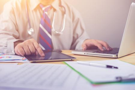 男性医師、医学生や患者、テスト結果、患者登録、選択と集中のデジタル システム サポートと健康チェック、会議中にタブレットとラップトップを