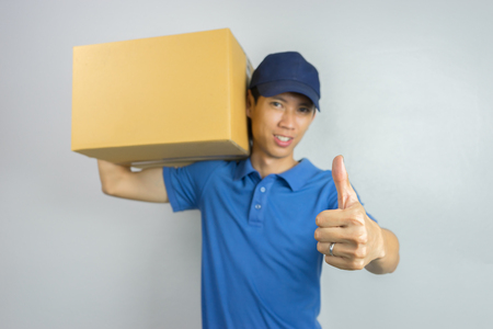 The best delivery service. Cheerful young asain man courier holding a cardboard box and showing his thumb up while standing against white background,selective focus