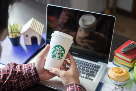 tokyo, Japan - Oct 20, 2016 : A man grabbing Starbucks paper coffee cup while using labtop pc and smart phone with another hand on the table in work space of Starbucks coffee shop,business meeting