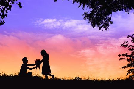 배경으로 태양이 석양에 결혼을 요구하는 남자 실루엣 제안, 무릎을 꿇고 꽃을 맺고 그의 여자 친구에게 약혼 반지를 줘.