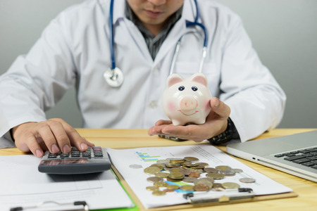 money, home, finance and relationships concept - Doctor holding out your piggy bank wanting payment Savings Pay Bill,Stethoscope financial checkup or saving for medical insurance costs with calculator Imagens - 72636224